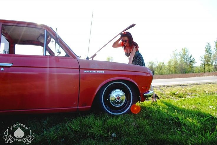 pretty redhead girl checking out datsun 510 engine