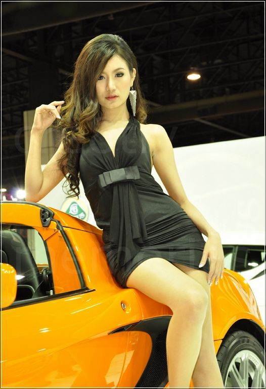hot babe in black dress next to lotus elise
