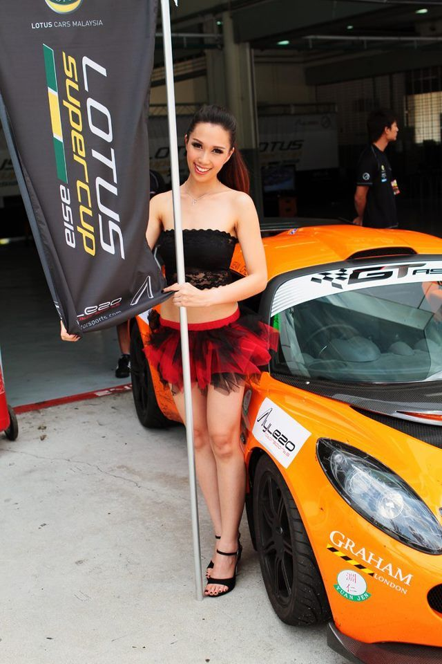super skinny girl next to lotus exige