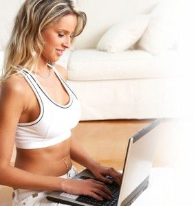 Girl in white tank top working on laptop computer